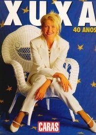 Xuxa sentada em cadeira branca, capa do especial de 40 anos da apresentadora, na revista Caras