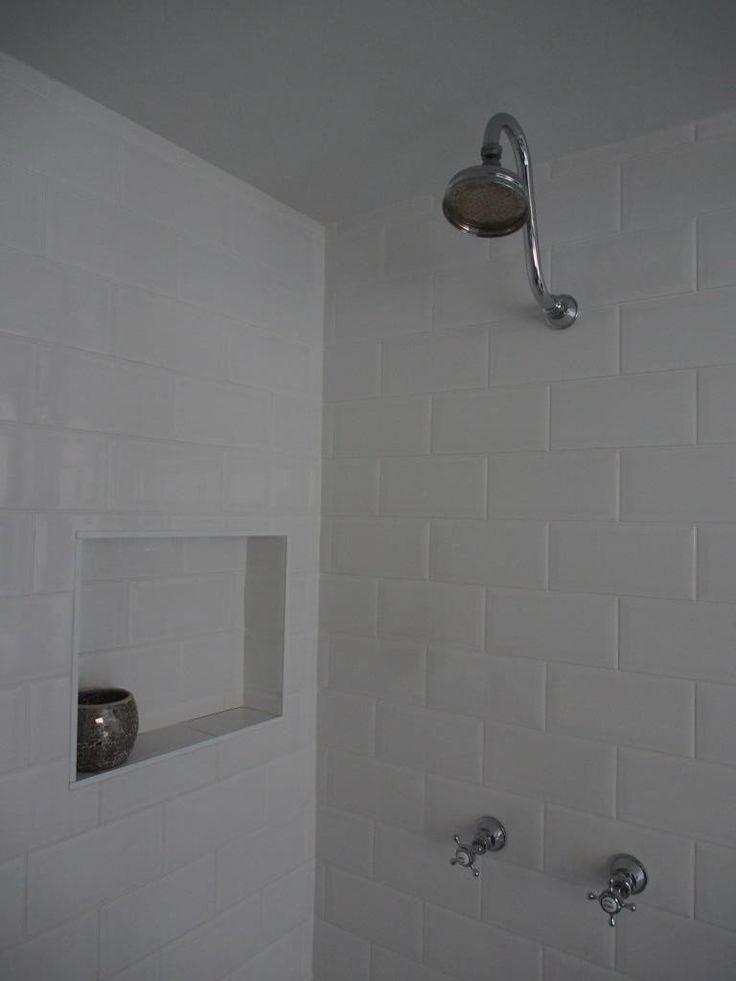 Goose-neck shower head, traditional tapware, tiled shower niche, beveled edge subway tiles.