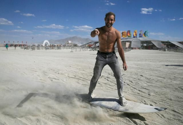 Burning Man participant Marshall Mosher from Atlanta surfs through the desert dust on a motorized surfboard on wheels past Center Camp. REUTERS/Jim Bourg
