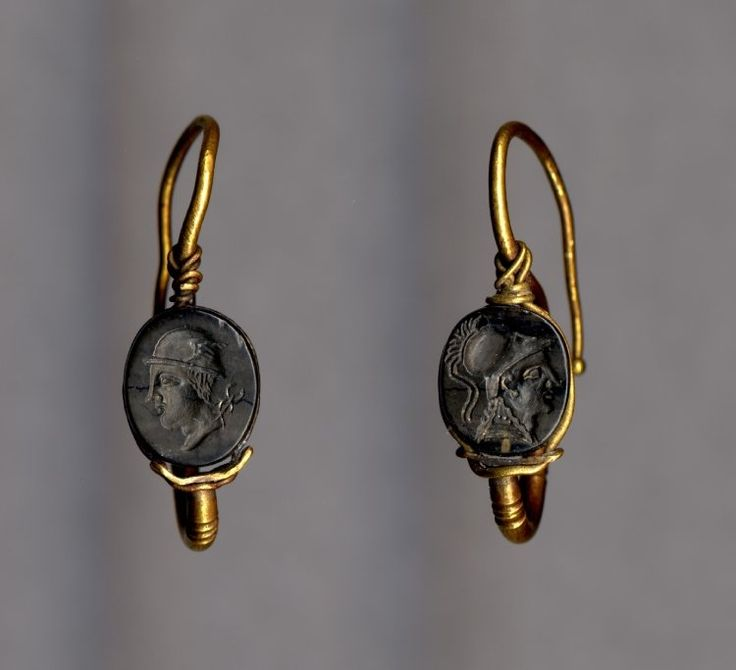 Gold earrings, set with a black glass seal engraved with a head of Athena wearing a crested Corinthian helmet. Roman period.