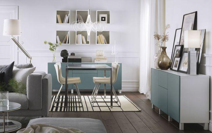 Séjour avec coin à manger meublé avec table en chrome et verre blanc, et chaises en chrome et cuir blanc. Meubles de rangement en blanc avec portes et faces de tiroir en gris-turquoise.