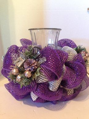 Se trata de un hermoso color púrpura y plata Navidad centro de mesa. Se hace con una canasta de alambre que puede contener un Portavelas grande o un florero. Se hace con malla metálica deco con decoración de Navidad agrega a juego. Mide aproximadamente 8 pulgadas de alto y 13 pulgadas de ancho. La abertura de la cesta es de 5 pulgadas. Para la imagen he utilizado un jarrón huracán. El huracán florero y la vela no está incluido en el listado