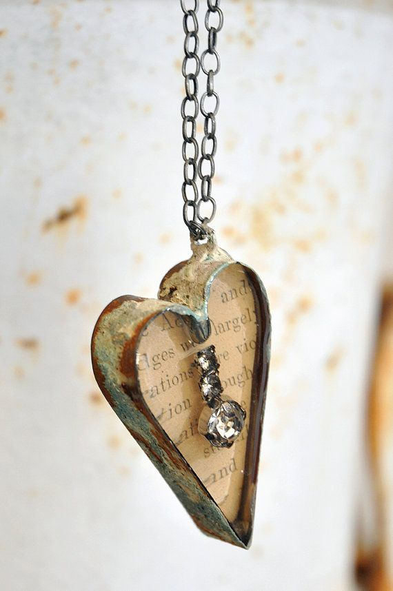 An industrial style hand forged metal heart, inset with vintage rhinestones and antique paper. This pendant is reversible with vintage