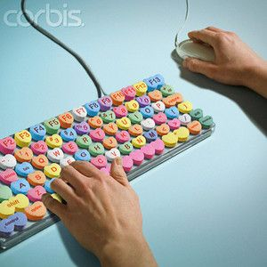 Man typing on computer keyboard candy hearts - Rights Managed - Corbis