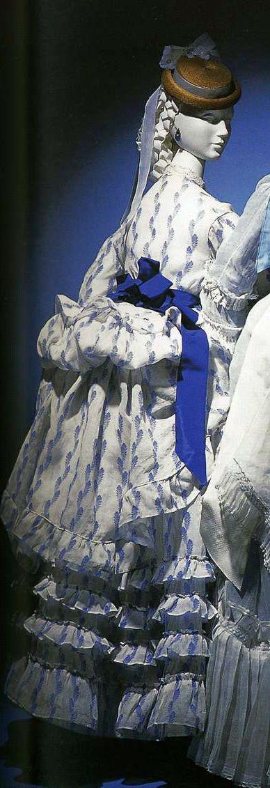 Дневное платье. 1870-1874. Белая льняная ткань органди с набивным рисунком из голубы полосок, комплект из корсажа и юбки, украшение оборками и воланами.