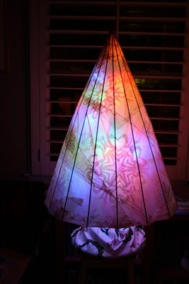 Christmas tree made with old umbrella frame modpodged with old sewing patterns....and lit from inside with led Christmas lights.