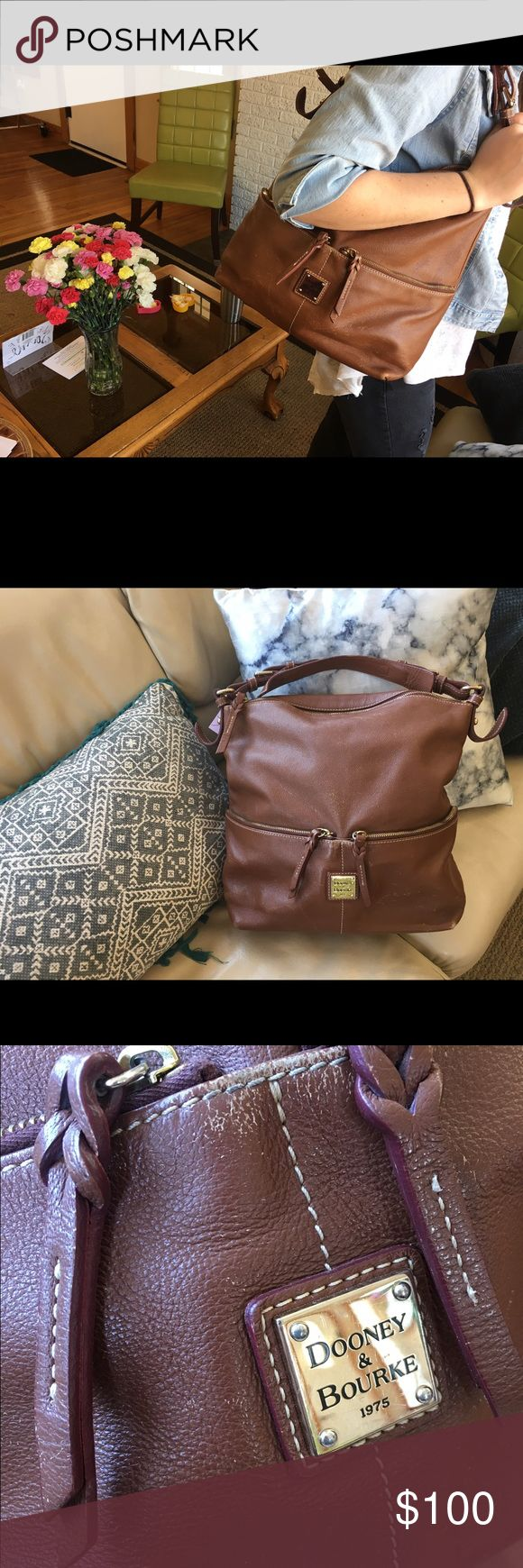 Classic Dooney and Bourke hobo handbag Used Dooney and Bourke bag -Some signs of wear on front(see picture) -paint spots on bottom interior                          Still a great brand name purse to use and for a good price! Dooney & Bourke Bags Hobos