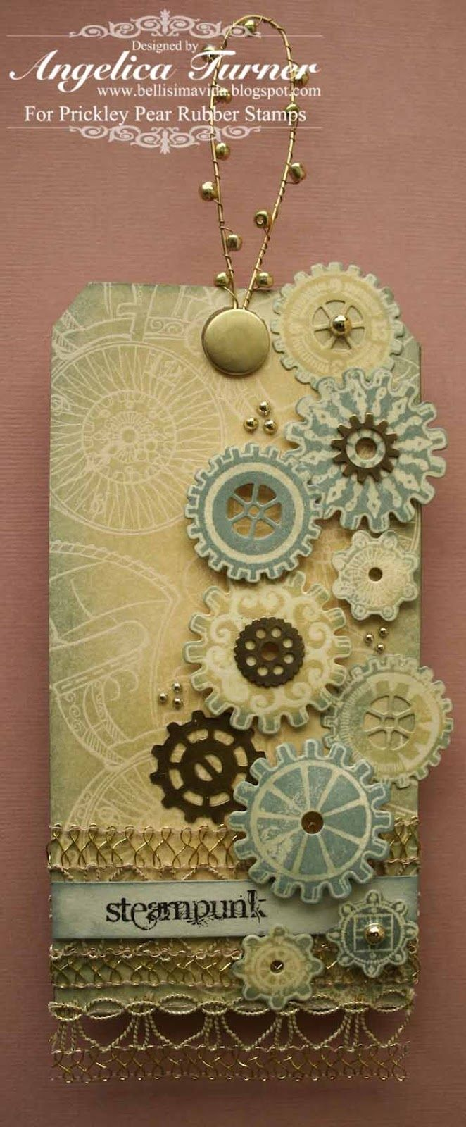 Light blue cream, gold and brown steampunk tag. Gives it more of a wedding look. Clock work cogs. Gold lace and brads. Chain on top.