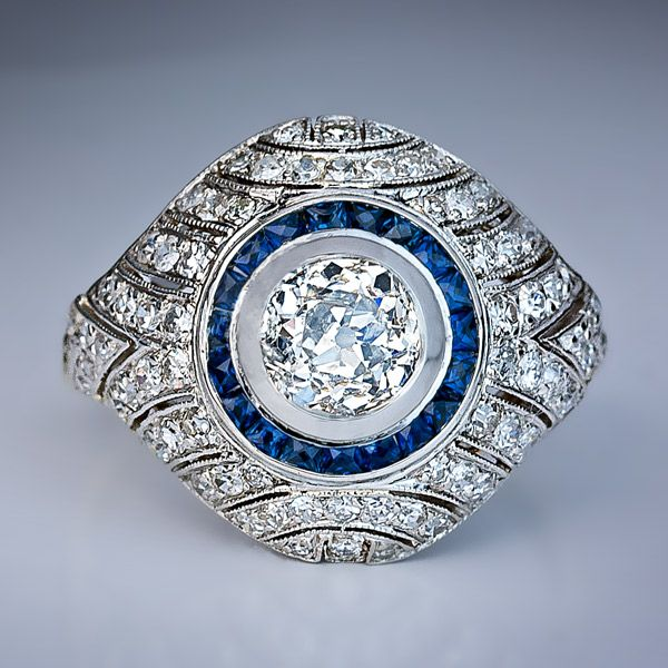 A Vintage Art Deco Diamond Sapphire Bombé Ring, Circa 1920s. The ring is crafted in white gold, with a sparkling bezel-set old mine cut diamond at the center encircled by a row of channel-set calibré cut sapphires, all set atop a diamond encrusted dome.