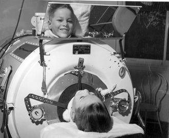 A dozen children in iron lungs line the hall of Herman Kiefer Hospital in Detroit, recovering from an infection that has paralyzed their respiratory system.