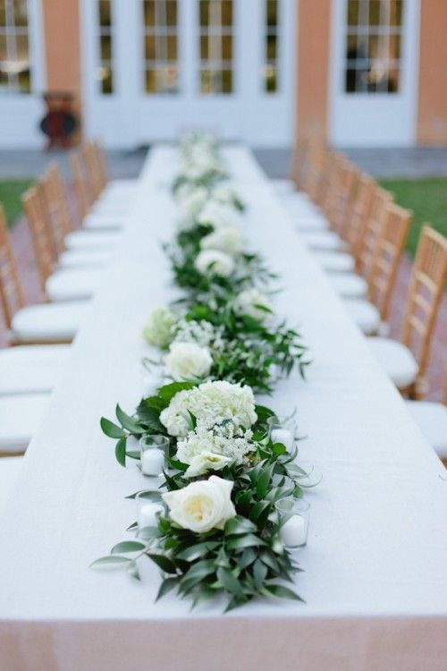 Utilizing the embroidered table runners makes me like these Wedding Table Garlands, as if flowers are coming out of the runners, and not having a container of any kind visible. I like the greenery in this, is it olive?