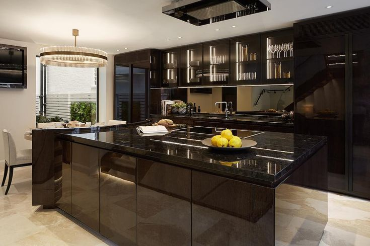 One of our bespoke kitchens in high gloss stained oak with bronzed glass and mirror. We design all of our own kitchens to give us complete freedom with the finishes and details so that theyre cohesive with the rest of the joinery design #kitchendesign #interiorarchitecture #interiordesign #interiorstyling #luxuryinteriors #laurahammett