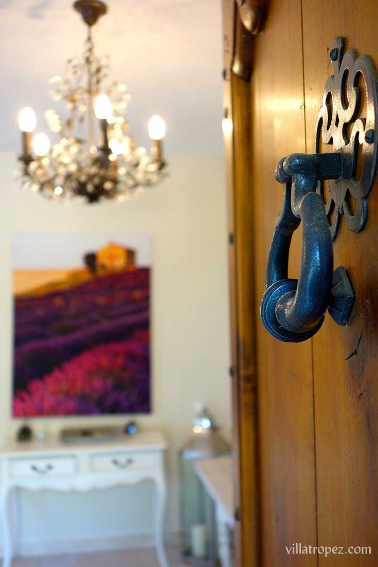 What an entrance into a luxury Provence rental villa. It's got it all: a traditional french oak door with wrought iron knocker, lit by a vintage chandelier and wall decor of the most famous landscape images of Provence - lavender fields. www.villatropez.com