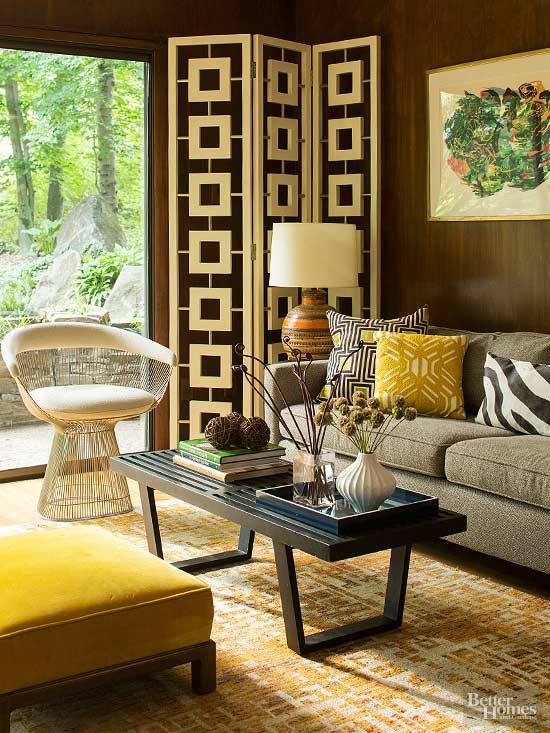 Bold-pattern throw pillows accent the rich wood paneling on the den's walls. Colors are pulled from artwork to bring the carpet, ottoman, table accents, and other furnishings together./