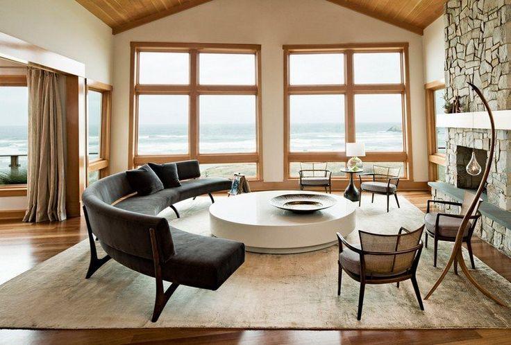 salon contemporain aménagé avec un canapé demi lune gris foncé, une table basse ronde et blanche et une cheminée habillée de pierre naturelle