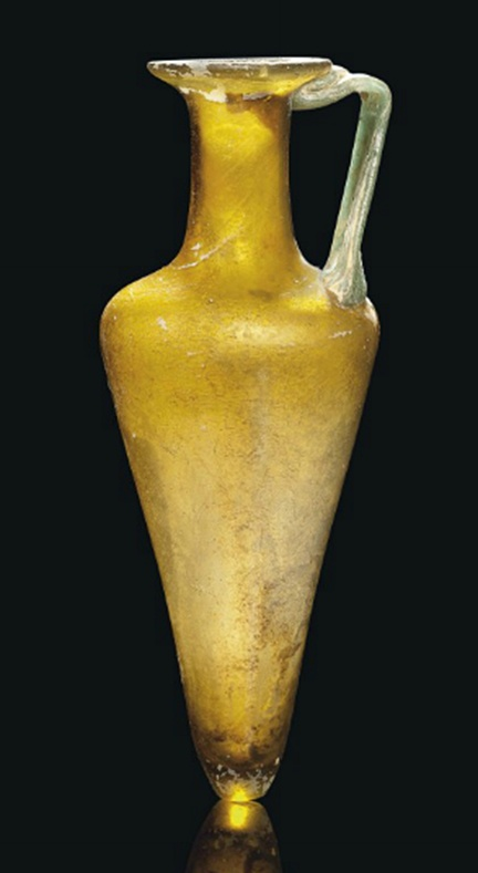 A ROMAN AMBER GLASS FLASK   CIRCA 2ND-3RD CENTURY A.D.   With tapering piriform body, angled shoulder, tall cylindrical neck and everted rim, green glass strap handle applied at shoulder and below rim  9 in. (23 cm.) high