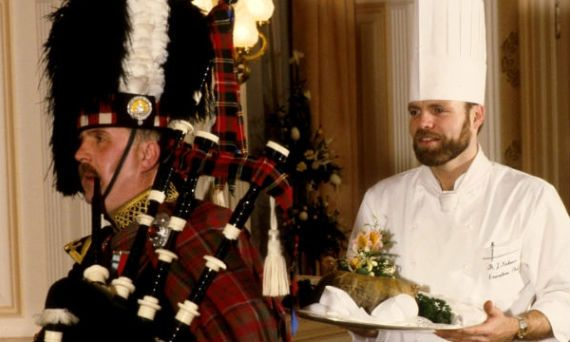 Celebrate Burns Night on January 25th with proper Burns Supper -- A piper in full Highland Regalia pipes in the haggis which is being carried on a tray by the chef behind him.