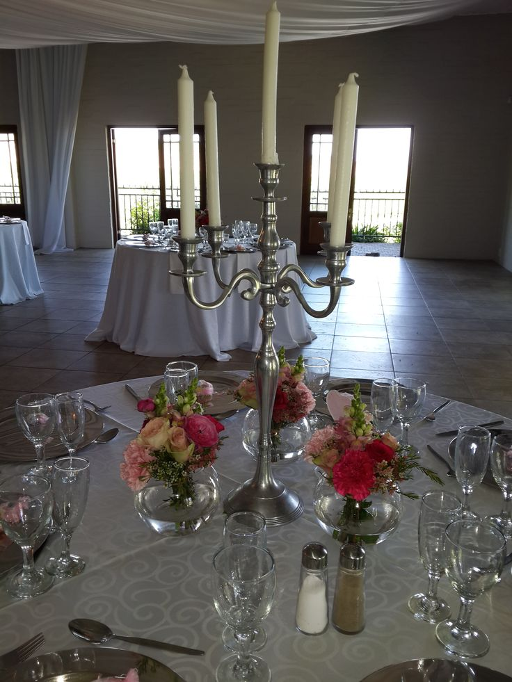 Silver candelabra with small bowls of flowers around it with different shades of pink