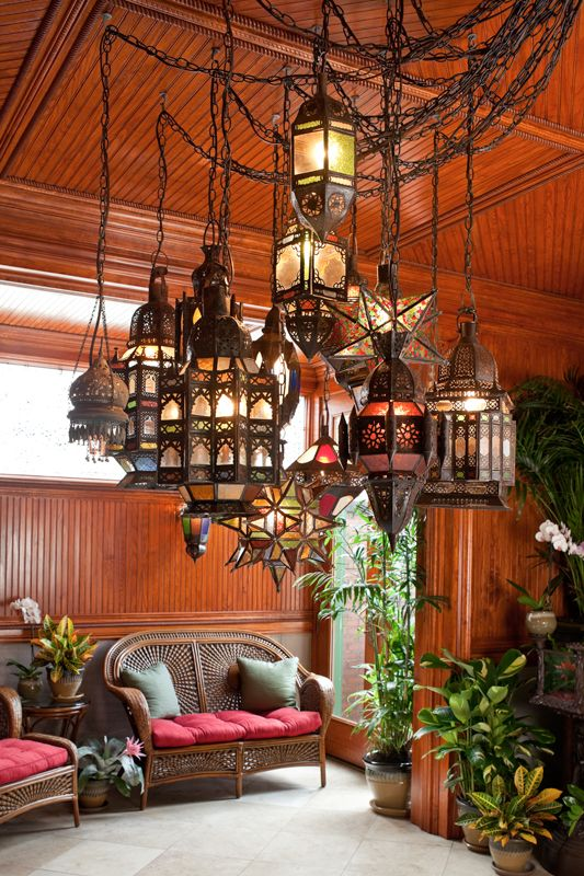 An exotic chandelier set made up of antique Moroccan lanterns hangs from the ornamental beadboard ceiling in a beautiful space. #Modern #MoroccanDecor #HomeDecor #Moroccan #Lanterns #interiors #interiordesign #Decor.