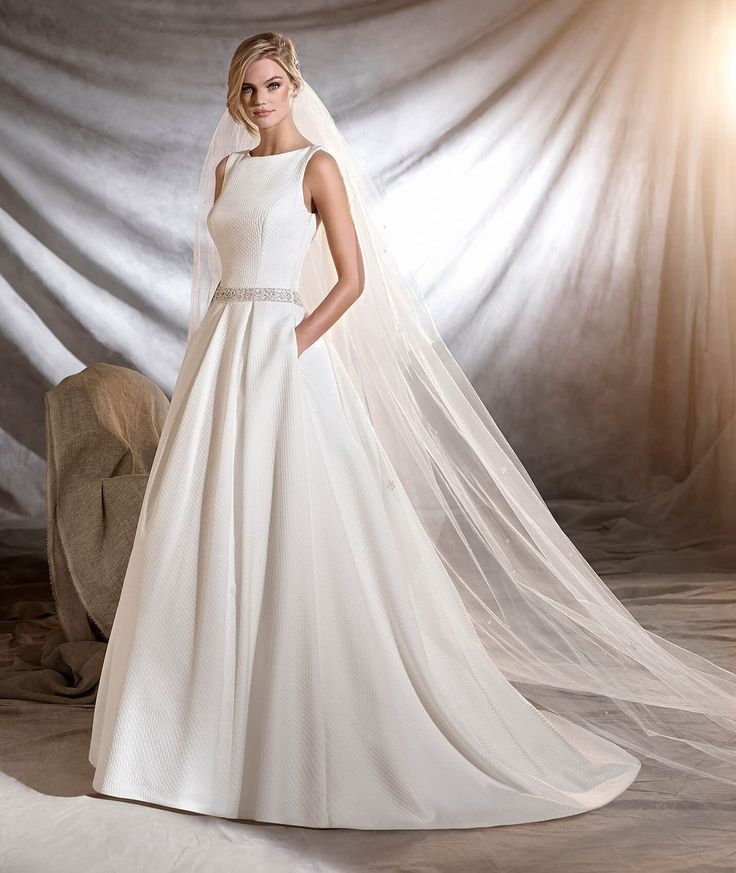Olmedo is a princess wedding dress in pique and tulle with elegant gemstone details. See this wedding dress by visiting the Pronovias website.