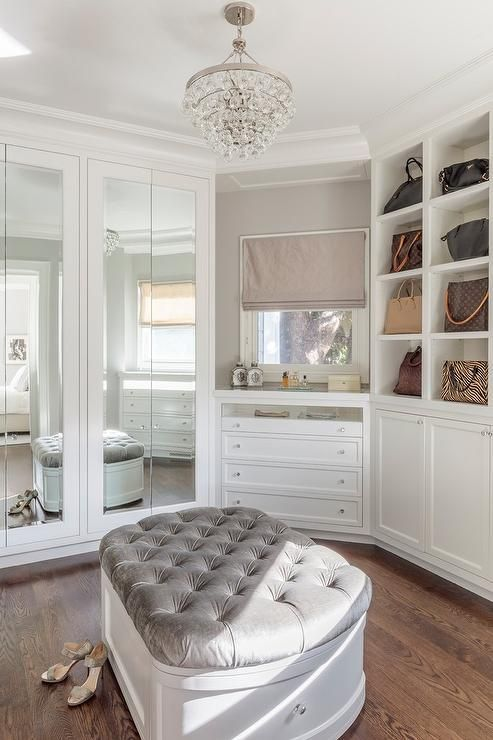 A dreamers walk in closet consists of luxury storage, elaborate shelf options and lots of space! This gorgeous white custom built-in walk-in closet showcases a Robert Abbey Bling Chandelier over a gray velvet tufted storage bench surrounded by mirrored closet doors, a window over makeup vanity with a blush pink roman shade, and modular shelves boasting a set of designer handbags.