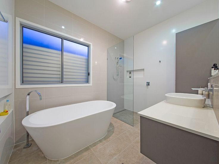 Modern bathroom.  The large open shower uses a frameless glass screen & has a tiled recessed shelf. Contrasting floor to ceiling tiles break up the large space nicely. The clients wanted a designer freestanding bath tub and long vanity basin and tiled shelf. An aluminium window screen gives plenty of privacy.  For more bathroom photos by Empire Design & Drafting visit www.empiredesigns.com.au