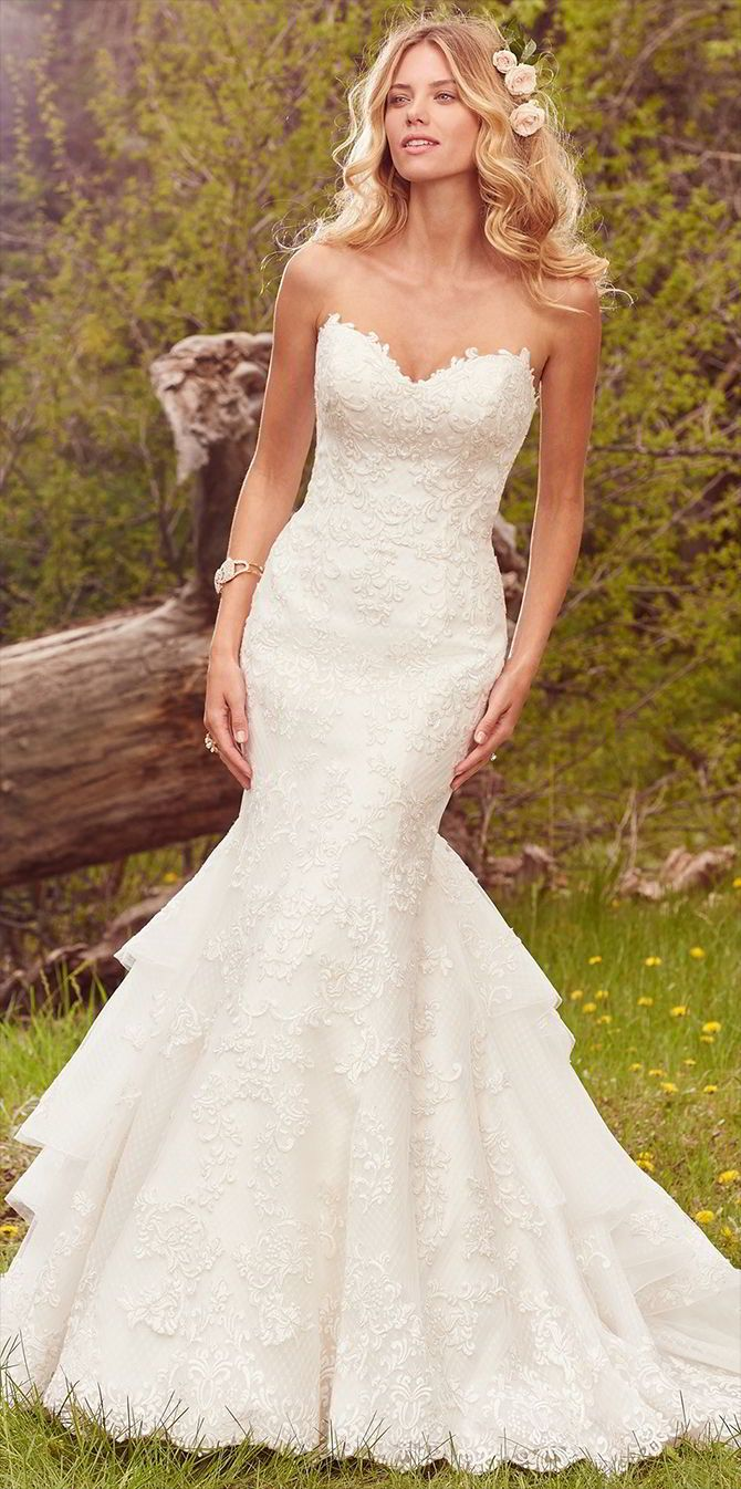 This glamorous fit-and-flare features a layer of lace motifs atop crosshatched tulle, complete with a gorgeous layered train and strapless sweetheart neckline.
