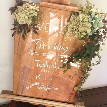 カフェの看板のようなおしゃれで可愛いウェルカムボード。 木に直接文字を書くのではなく、上にアクリル板のようなツヤツヤな素材を持ってくることでよりおしゃれになりますね! 木のイーゼルで素材を合わせれば、ナチュラルに統一感のある素敵なウェルカムボードの完成です。