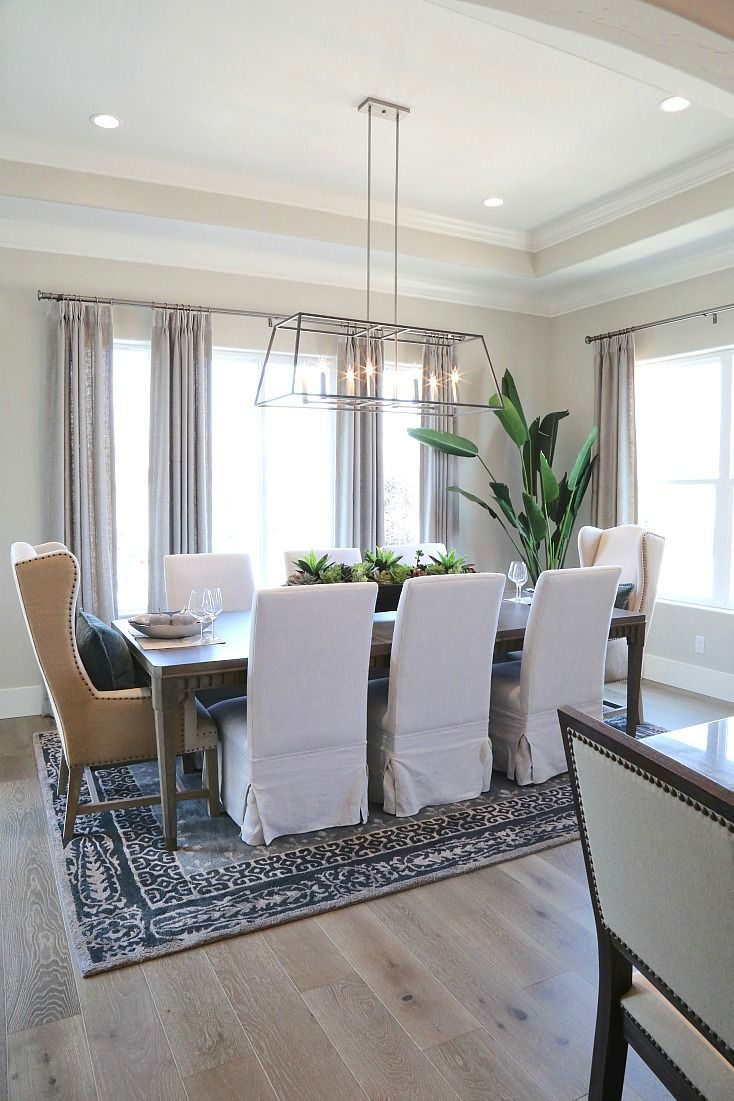 Neutral dining room with mixed chair styles and beautiful lighting.