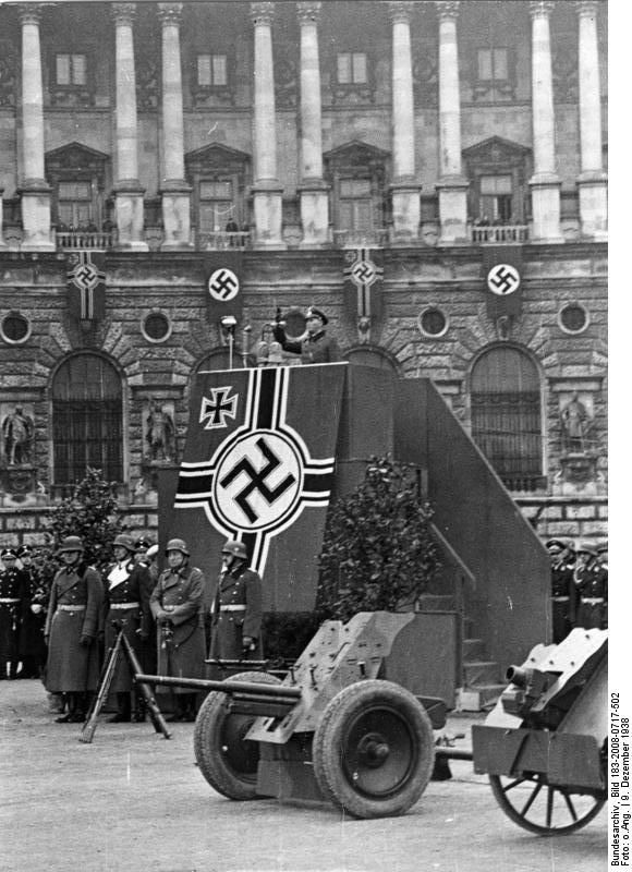 German Army General Werner Kienitz speaking to recruits at the Heldenplatz in Vienna, Austria, 9 Dec 1938; note 7.5 le.IG 18 infantry guns on display Source	   	German Federal Archive