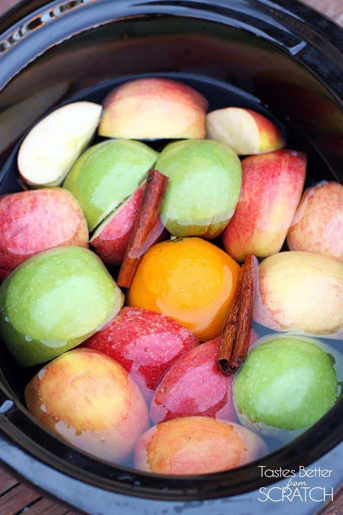 A slow cooker filled with apples, oranges, and cinnamon sticks.