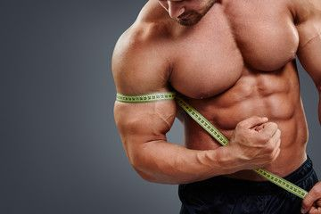 Closeup sexy fitness male model measuring bicep with tape measure isolated over gray background. Bodybuilder tries to measure bicep by himself.