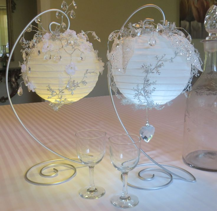 Elegant table decoration made with white paper lanterns, embellished with silk flowers and lots of sparkle incl. a battery pack with LED lights that bring your event to LIGHT!!