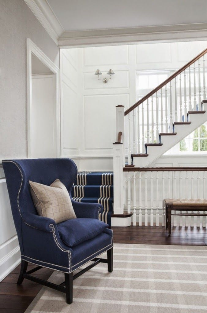 VT Interiors shares this photo of the downstairs landing with striped carpeting leading to a comfortable, Queen Anne reading chair, upholstered in a durable fabric.