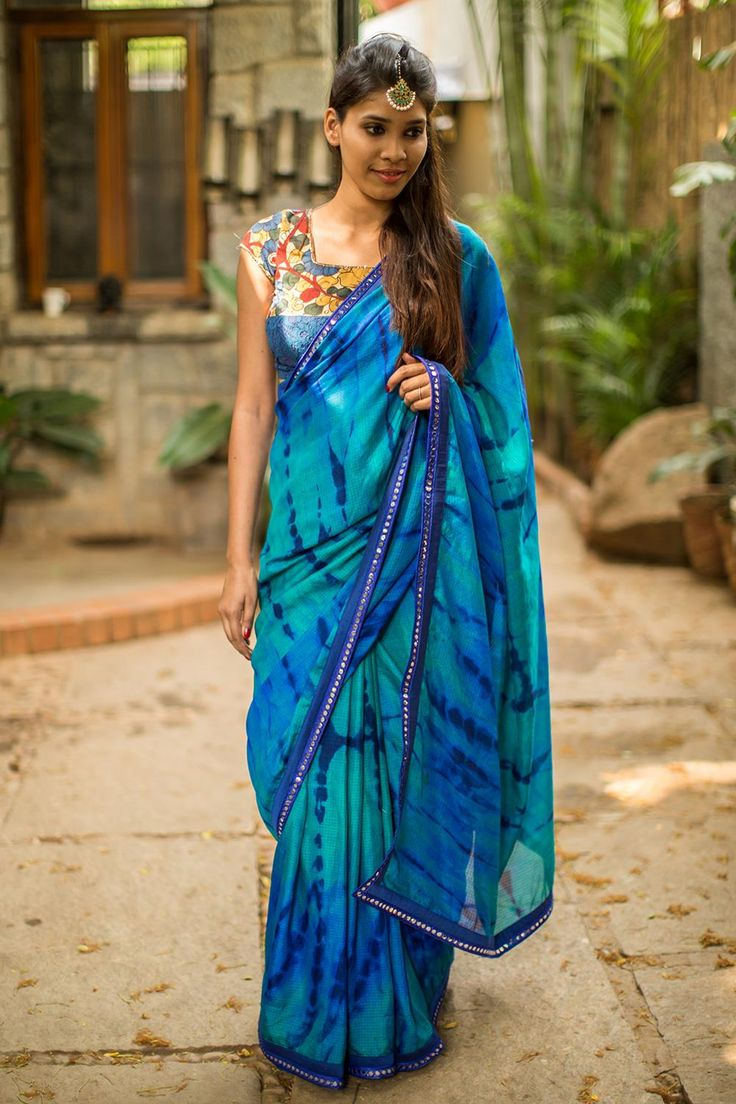 Did somebody say 'Shibori'? We cannot stop crushing on all manner of attractive Shibori dyed ware! Two thumbs up to this Shibori dyed blue drape in semi kota doria fabric. You are bound to look forever trendy in this beautiful saree. Put your creative cap on and pair this wonder with a blouse of varied hues and textures. Or stay cool as ever in a blouse in any shade of blue. #kalamkari #saree #india #blouse #houseofblouse