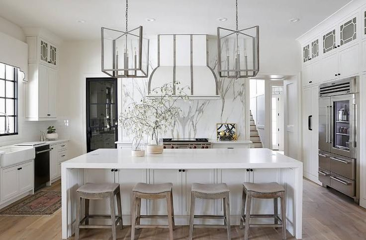 Eye-catching steel and glass lanterns hang over a white center island finished with a white quartz waterfall countertop seating gray saddle counter stools facing a gorgeous white dome hood accented with steel straps and fixed on a gray and white marble slab backsplash above a Wolf range.