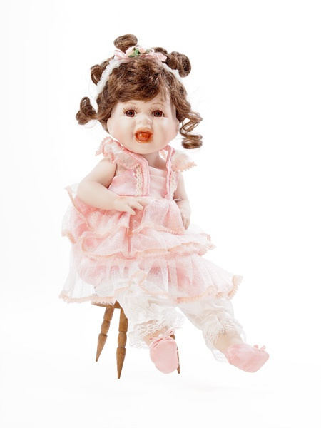 An all-Porcelain doll on a wooden chair.