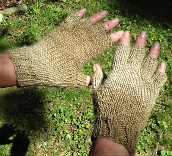 Half finger ladies gloves are hand knit in tonal tan 100% pure baby alpaca yarn. These ladies half finger gloves are knit with ribbing at the wrist for a close, warm fit, and smooth stockinette stitch throughout the rest of the glove for a classic, tailored look. This style of ladies glove includes a half thumb and four individual half fingers. The gloves leave fingertips free while providing warmth to the hand. If you have never worn alpaca before, you are in for a treat! This yarn is pure…