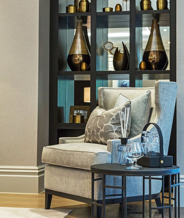 A stunning focal point in our latest Surrey project; the light dove grey hues of this exquisite @ZoffanyFW fabric chair contrast against the dark ebony shelving, warmed by the bronze tones of the carefully selected accessories.