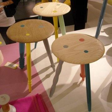 des tabourets en bois avec l'assise en bois clair brut et les pieds peints en couleurs laquées de 3 couleurs différentes à chaque fois.