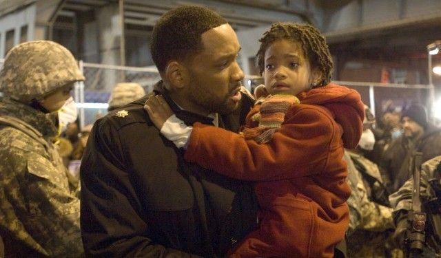 """Robert Neville (Will Smith) hält Marley (Willow Smith) auf dem Arm, während im Hintergrund Soldaten mit Atemschutz stehen; undatierte Filmszene aus dem Film """"I am Legend"""" von Robert Neville aus dem Jahr 2007 (picture-alliance/ dpa)"""