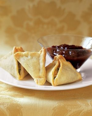 Easy Samosas - 1  tablespoon  olive oil; 1  medium onion, chopped; 1 1/2  teaspoons  curry powder; Kosher salt and black pepper; 2  cups  store-bought refrigerated mashed or frozen mashed potatoes, thawed (about 16 ounces); 1  10-ounce package frozen peas, thawed; 1  15-ounce package refrigerated piecrusts