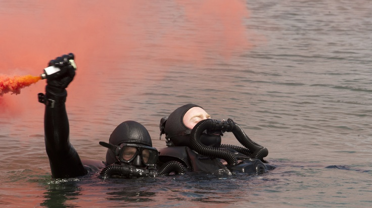 CORONADO, Calif. (April 26, 2012) A Basic Underwater Demolition/SEAL (BUD/S) candidate waves a flare during a simulated dive casualty drill while training at Naval Amphibious Base Coronado. Dive training is the second phase candidates participate in during BUD/S. The Navy SEALs are the maritime component of special operations forces and are trained to conduct a variety of operations from the sea, air and land. (U.S. Navy photo by Mass Communication Specialist 2nd Class Dominique M. Canales