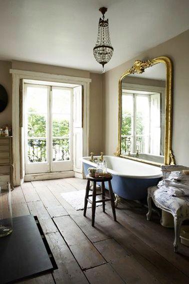 Dans une salle de bain rétro, un grand miroir ancien, un fauteuil de style donne tout de suite le ton ! Ajoutez une baignoire sur pieds avec une coque de couleur bleu pour contraster avec une sol en parquet l'harmonie sera parfaite