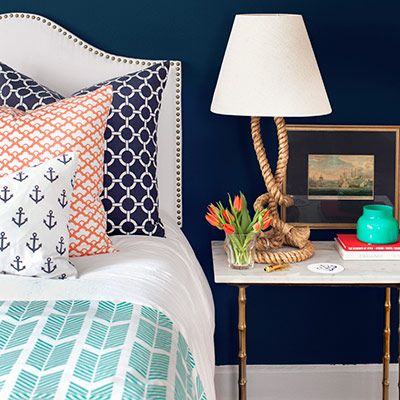 Royal Blue & Coral & Teal: The dark blue walls are like the vast sea upon which the lighter colors in this nautical bedroom float. There's a perfect play of patterns and textures. I especially love the coastal reference in the rope lamp stand and table legs.