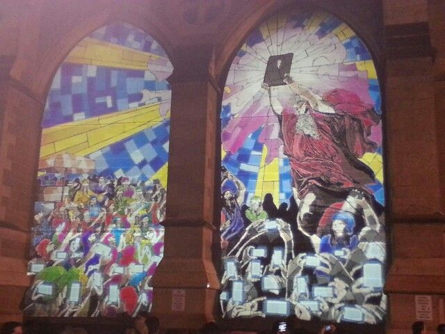 Night installation on a church windows of Moses recieving a 'Tablet' and the crowed are taking pix with their smartphones...