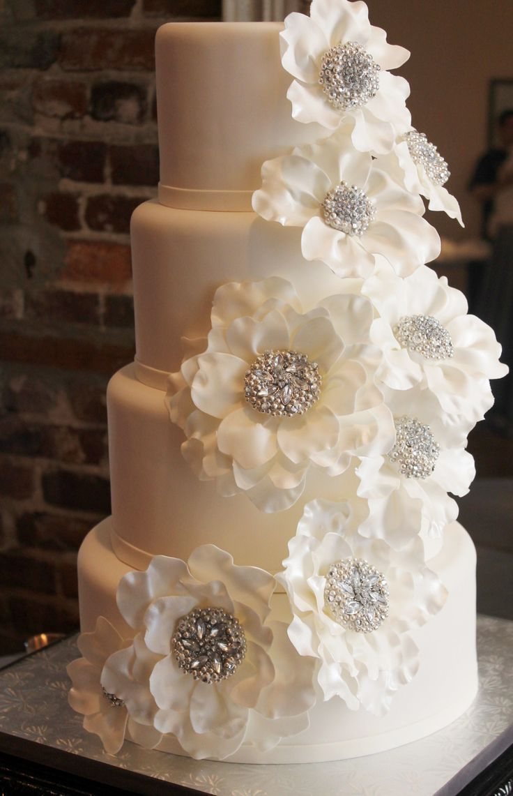 Handmade jeweled flower centers create the look of the bride's couture wedding dress details.  The delicate white petals simulate ribbon used in millinery flowers.