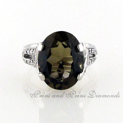 """Centre stone is a 8.70ct oval cut smokey topaz with 26 = 0.24ct GH/SI round brilliant cut diamonds set in an 18k white gold """"criss-cross"""" band"""