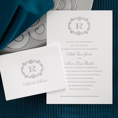 A Simple, White Invitation Card Features A Single Initial Monogram Printed  At The Top With