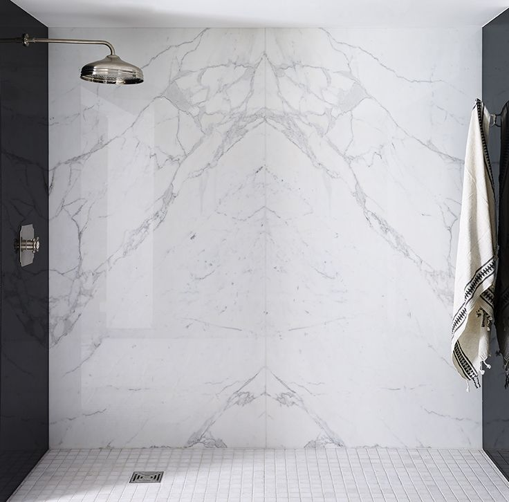 Statuario Venato marble shower walls. Book matched. Featuring Nero Absolute Polished Granite ties. Stunning. Mandarin Stone.